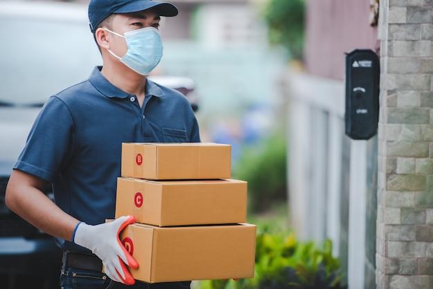 Personel dostawy niosący pudełka papierowe. noś rękawice medyczne i maski, aby chronić covid-19