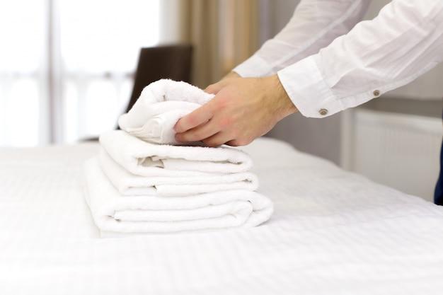 Personel hotelu ustawia poduszkę na łóżku