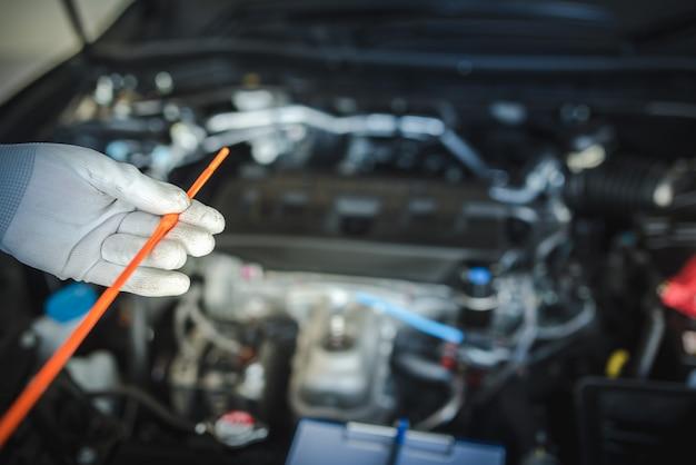 Personel mechanika samochodowego podnosi wskaźnik poziomu oleju, aby sprawdzić poziom oleju. aby sprawdzić stan samochodu
