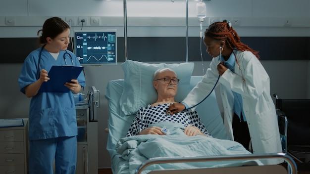 Personel medyczny konsultujący chorego pacjenta na oddziale szpitalnym