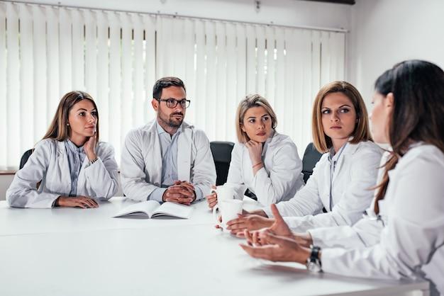 Personel medyczny podczas spotkania w sali konferencyjnej.