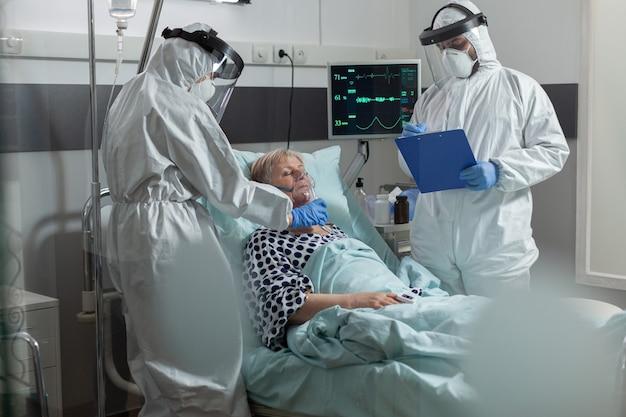 Personel medyczny w kombinezonie ppe pomagający pacjentowi oddychać z maską tlenową