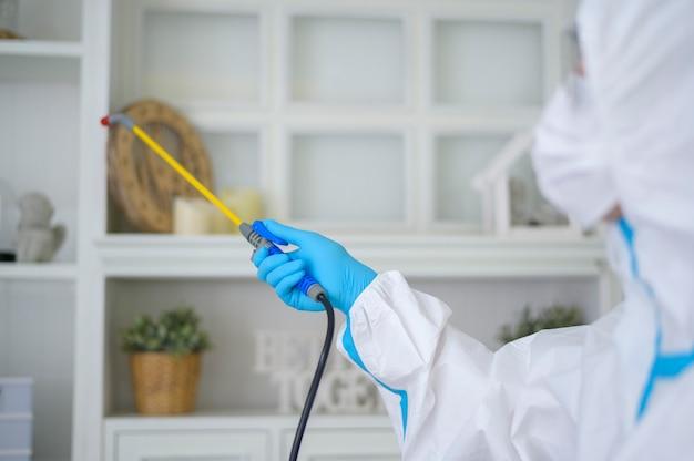 Personel medyczny w kombinezonie ppe używa sprayu dezynfekującego w salonie, ochrona covid-19, koncepcja dezynfekcji.