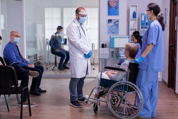 Personel medyczny z maską ochronną rozmawia z niepełnosprawną kobietą w recepcji szpitala, podczas gdy pacjenci czekają na badanie