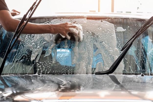 Personel myjni używa gąbki do czyszczenia przedniej szyby samochodu.