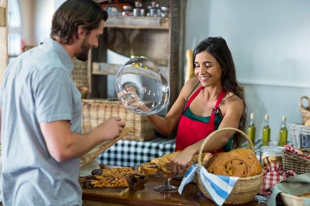 Personel piekarni pokazuje przekąskę klientowi płci męskiej przy ladzie