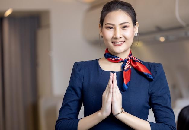 Personel pokładowy lub stewardessa wita pasażerów na pokładzie samolotu, stewardesa lub stewardesa