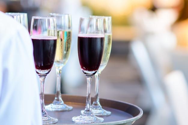 Personel restauracji trzyma kieliszek wina gotowy do podania na przyjęciu