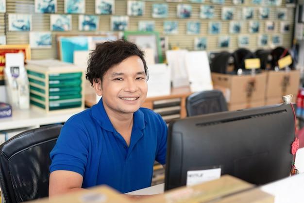 Personel serwisu samochodowego w niebieskim mundurze i uśmiechnięty wita klientów w warsztacie samochodowym
