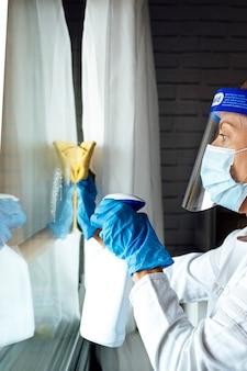 Personel sprzątający dezynfekujący dom przed wirusami, noszący przezroczystą maskę ochronną