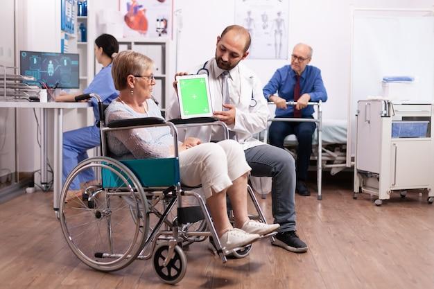 Personel szpitala konsultuje niepełnosprawną starszą kobietę siedzącą na wózku inwalidzkim, trzymającą tablet pc z zielonym ekranem