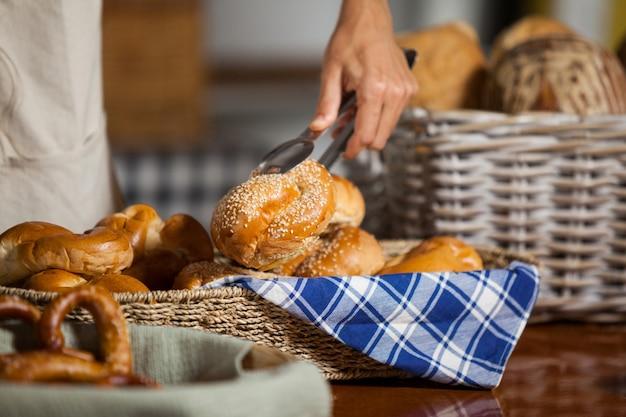 Personel trzymający chleb z szczypcami w piekarni