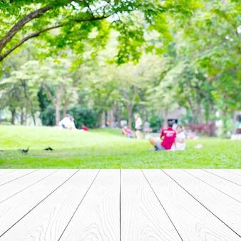 Perspektywa białego drewna na rozmycie streszczenie zielone drzewa pozostawia naturę z ludźmi