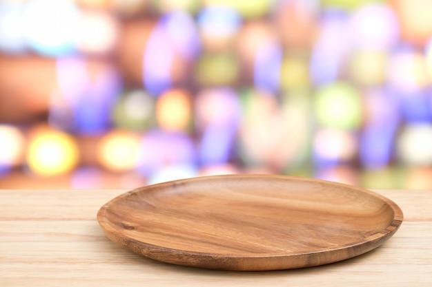 Perspektywa drewniany stół i drewniana taca na górze nad rozmyciem tła światła bokeh