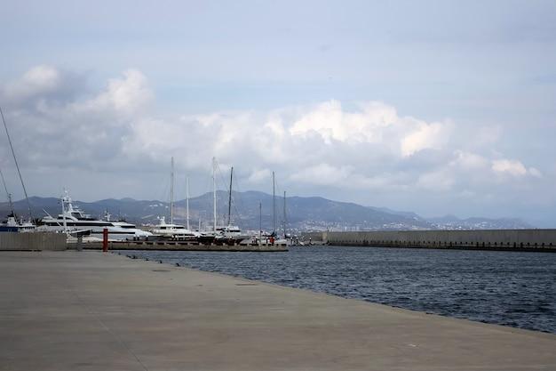 Perspektywa morza ze statkami na powierzchni otoczonymi górami i chmurami