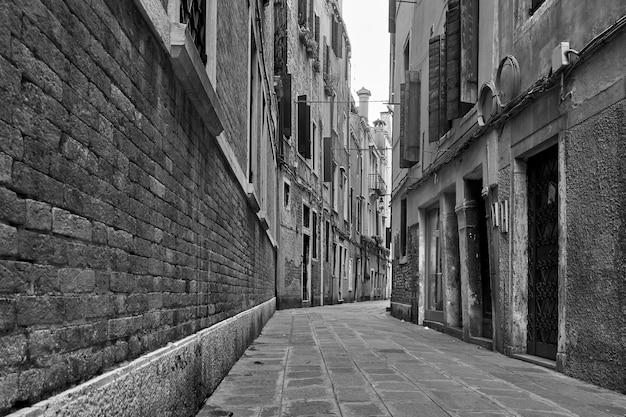 Perspektywa pustej ulicy w wenecji, włochy. czarno-biała fotografia miejska