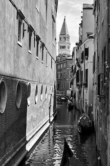 Perspektywa wąskiego kanału bocznego z gondolami w wenecji, włochy. czarno-biały wenecki pejzaż miejski