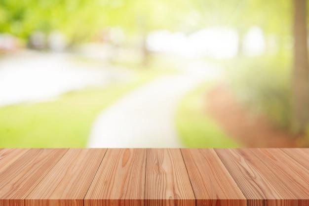 Perspektywiczny drewniany stół na górze nad naturalnym rozmyciem tła, może być używany do wyświetlania produktów montażowych lub projektowania układu.