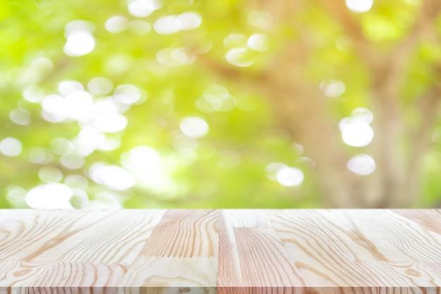 Perspektywiczny drewniany stół na górze nad plamy naturalnym tłem