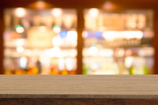Perspektywiczny drewniany stół na wierzchołku nad plamy wina barem w cukiernianym tle