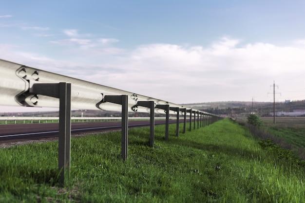 Perspektywiczny portret ogrodzenia ochronnego bariery drogowej w słoneczny dzień z błękitnym niebem.