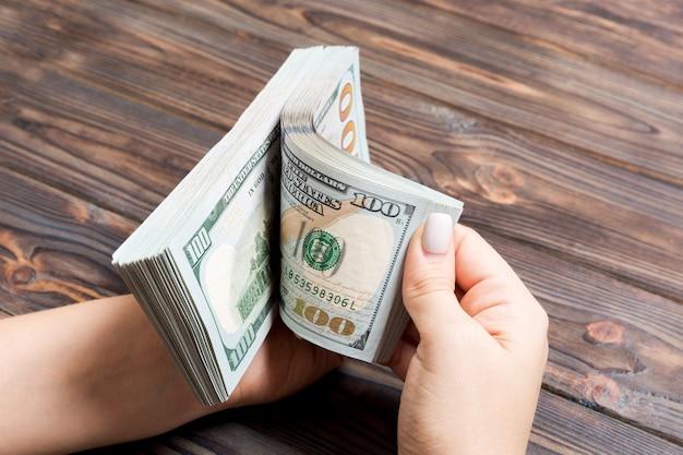 Perspektywiczny widok bizneswomanu ręki liczy sto dolarowych banknotów na drewnianym. koncepcja sukcesu i bogactwa