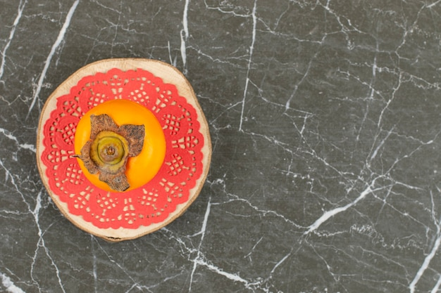 Persymona na różowej serwetce na drewnianym talerzu.