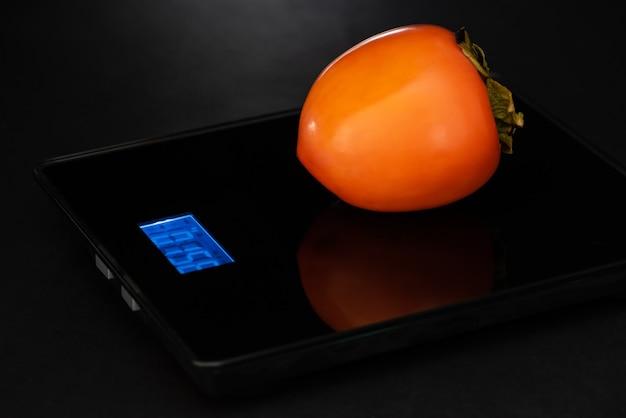 Persymona stoi na wadze elektronicznej na czarnym tle.