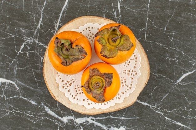 Persymony na białej serwetce na drewnianym talerzu.