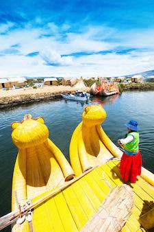 Peru - 11 maja 2015: niezidentyfikowane kobiety w tradycyjnych strojach witają turystów na wyspie uros