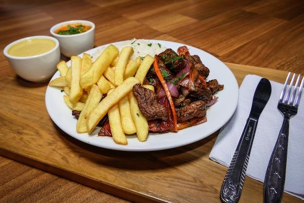 Peruwiańskie jedzenie lomo saltado, frytki z mięsem, cebulą, żółtą papryką, pietruszką, białym ryżem i sosem sojowym, na białym talerzu ze sztućcami i drewnianym tłem.