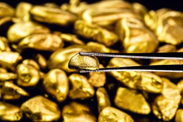Pęseta trzymająca błyszczącą bryłkę złota, koncepcja biżuterii i rudy oraz praca złotnicza