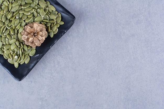 Pestki dyni i szyszka na talerzu na marmurowej powierzchni