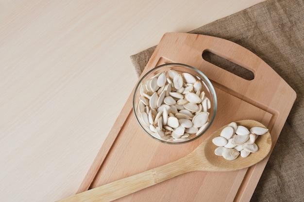 Pestki dyni w białej misce i łyżce na lnie na stole kopiuj przestrzeń