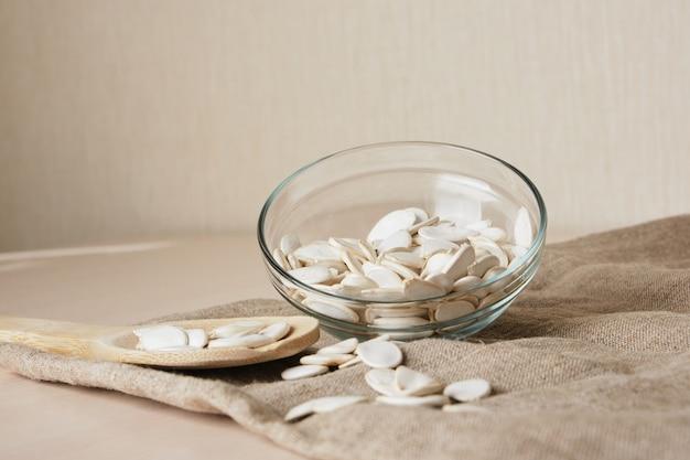 Pestki dyni w białej misce i łyżce na lnie na stole