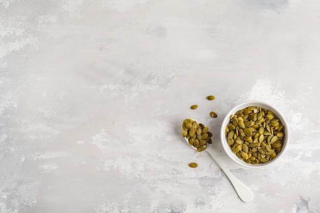 Pestki dyni w białej misce, widok z góry, kopia przestrzeń, tło żywności. koncepcja zdrowej żywności wegetariańskiej.