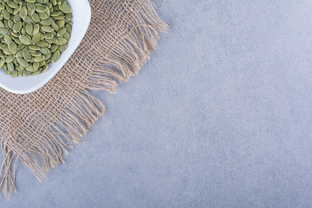 Pestki dyni w misce na jutowej serwetce na marmurowej powierzchni