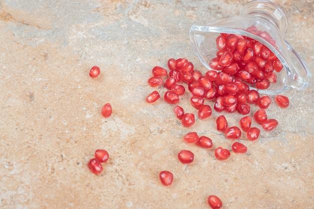Pestki granatu w szkle na marmurowej powierzchni.
