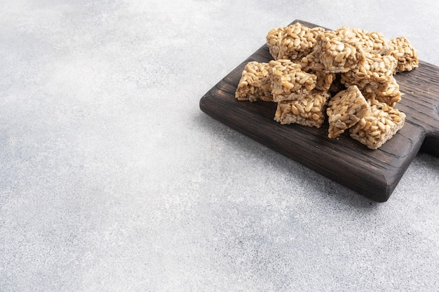 Pestki słonecznika w glazurze cukrowej, orientalna słodycz krucha. kozinaki są rozbijane na kawałki na drewnianej desce, kopia przestrzeń