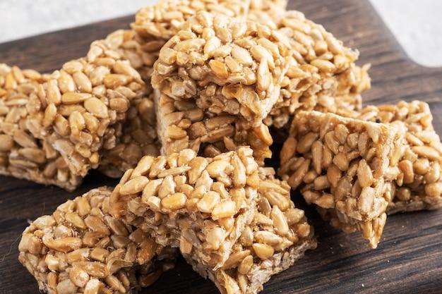 Pestki słonecznika w glazurze cukrowej, orientalna słodycz krucha. kozinaki są rozbijane na kawałki na drewnianej desce,