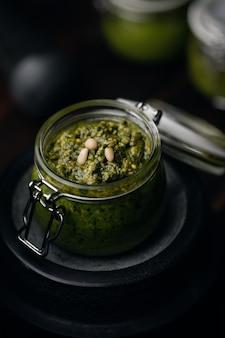 Pesto genovese - tradycyjny włoski sos z zielonej bazylii z orzeszkami pinii, bazylią i czosnkiem w szklanym słoju na ciemnym tle. kuchnia śródziemnomorska