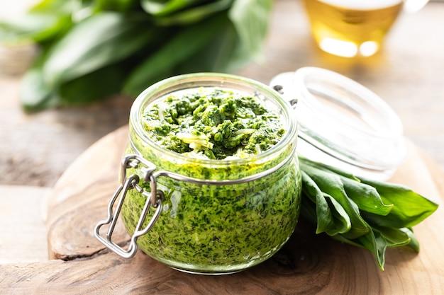 Pesto z dzikiego pora z oliwą z oliwek i parmezanem w szklanym słoiku na drewnianym stole.
