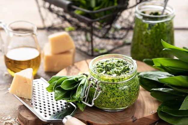 Pesto z dzikiego pora z oliwą z oliwek i parmezanem w szklanym słoju na drewnianym stole. przydatne właściwości czosnku niedźwiedziego. liście świeżego czosnku niedźwiedziego. poziomy