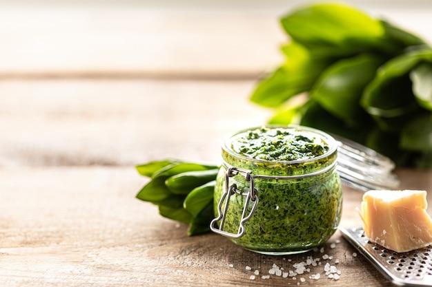 Pesto z dzikiego pora z oliwą z oliwek i parmezanem w szklanym słoju na drewnianym stole. przydatne właściwości ramson. liście świeżego ramsona. skopiuj miejsce