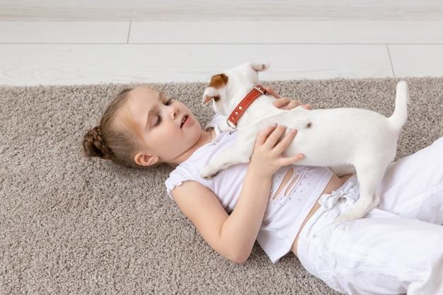 Pet, dzieciństwo i koncepcja zwierząt - portret dziewczynki dziecko leżące na podłodze z szczeniakiem jack russell terrier.