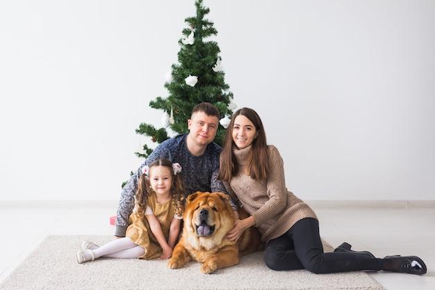 Pet, święta i świąteczna koncepcja - rodzina z psem leżą na podłodze w pobliżu choinki.