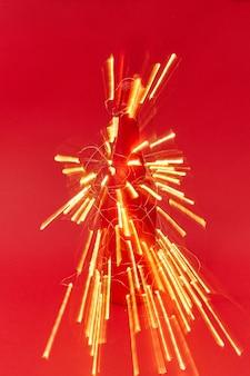 Petarda z zabłysniętych śladów lampek choinkowych na pomalowanej butelce wina na czerwonym tle z miejscem na kopię. karta z gratulacjami noworocznymi.