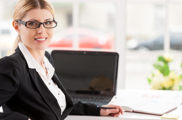 Pewna biznesowa dama. piękna dojrzała kobieta w stroju formalnym, patrząca przez ramię i uśmiechająca się siedząc w swoim miejscu pracy