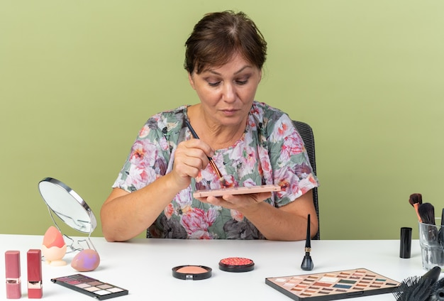 Pewna dorosła kobieta rasy kaukaskiej siedząca przy stole z narzędziami do makijażu, trzymająca pędzel do makijażu i patrząca na paletę cieni do powiek