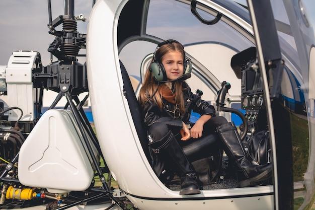 Pewna dziewczyna animowana w zestawie słuchawkowym pilota siedząca w kokpicie helikoptera